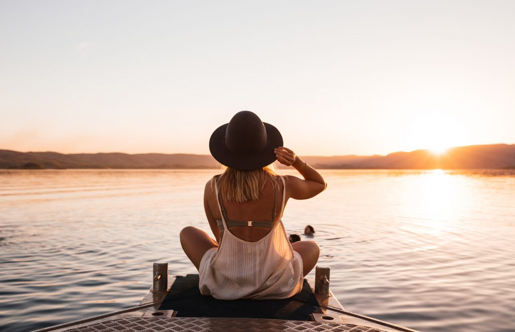 woman sitting lake pier surrounded by hills at sundown