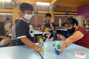 Children at Morning Star Community Services animating their paper robots with the help of a student-care teacher using a stop motion videography app on the smartphone. PHOTO: TRCL